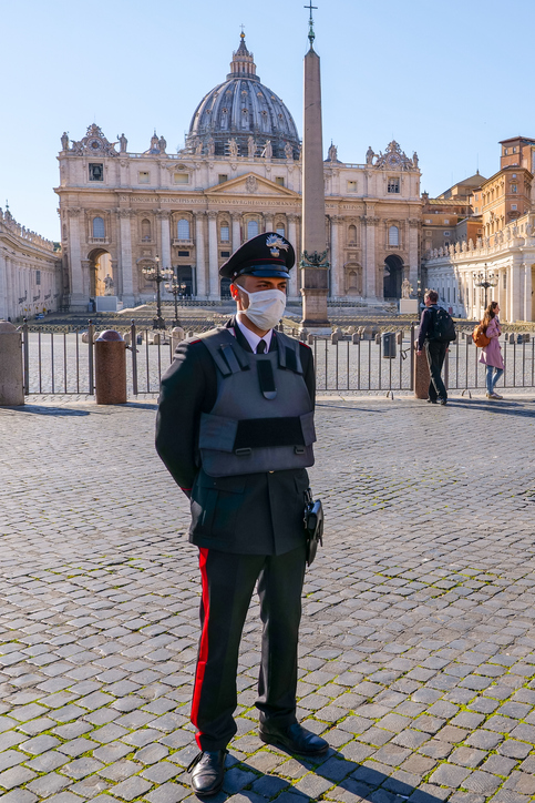 An Italian Policeman With Medical Mask Controls Access To The Square Of St. Peter's Basilica